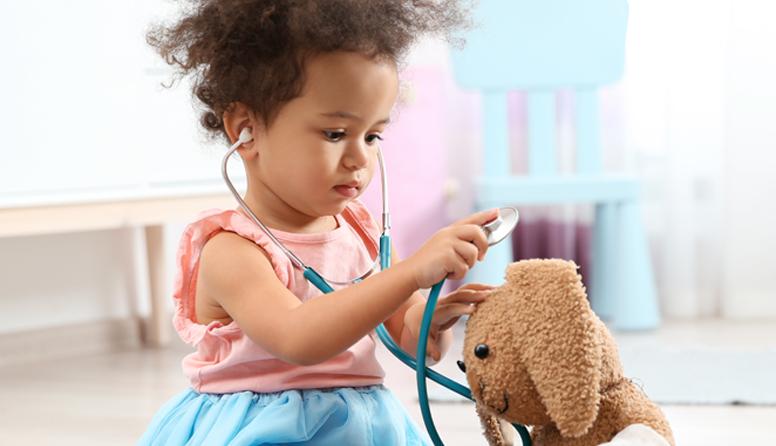 AseguMed seguro médico para hispanos - Niña hispana con vestido rosa y azul jugando ser doctora con su peluche en su habitación.