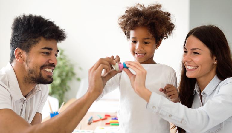 AseguMed aseguranza económica en USA - Padre y madre jugando con hija, sonriendo, vestidos en blanco en la sala