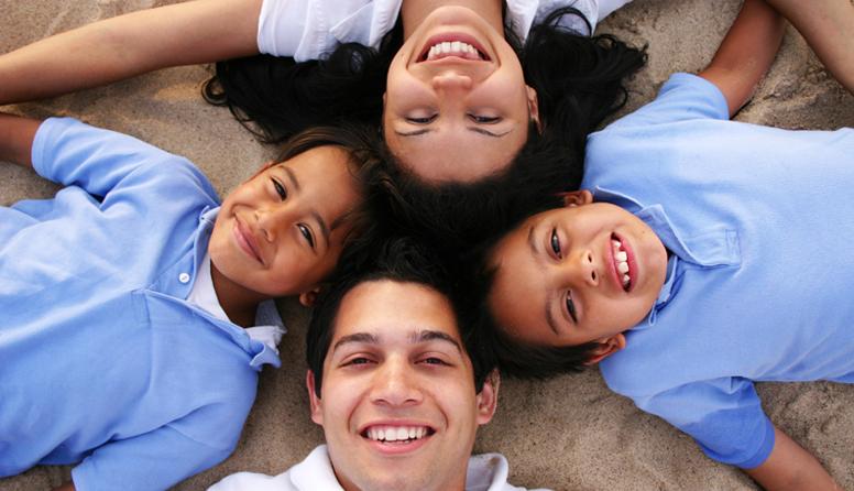 AseguMed seguro de salud a corto plazo - Familia hispana, padre, madre y dos hijos vestidos de azul tirados en la arena de la playa abrazados sonriendo